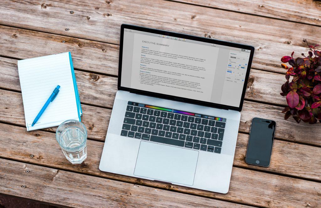 テーブルに置かれたパソコンとスマホとノート