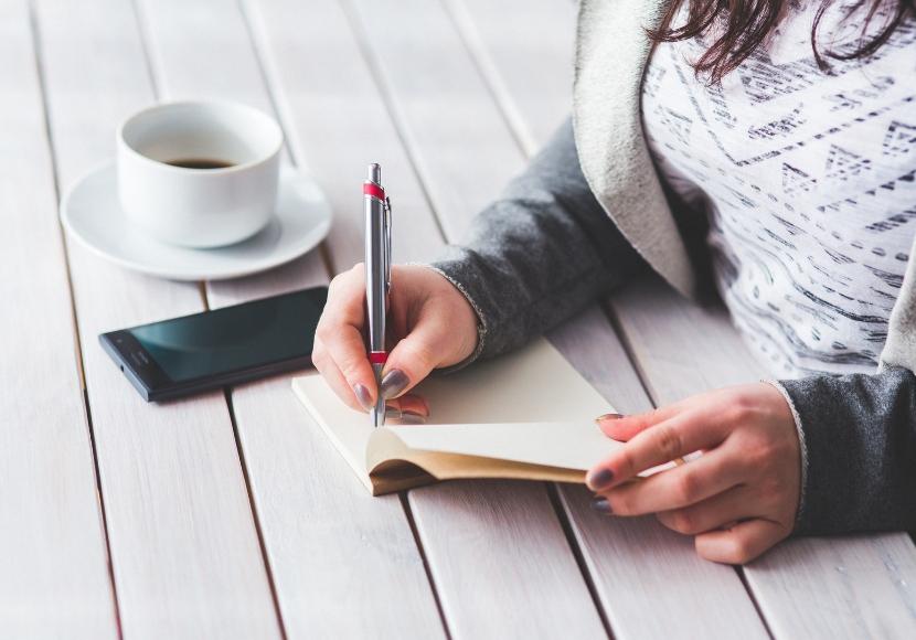 ノートにメモをする女性